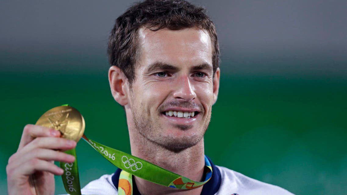 Andy Murray, of England, smiles as he holds up his gold medal at the 2016 Summer Olympics in Rio de Janeiro, Brazil, Sunday, Aug. 14, 2016. (AP Photo/Charles Krupa)