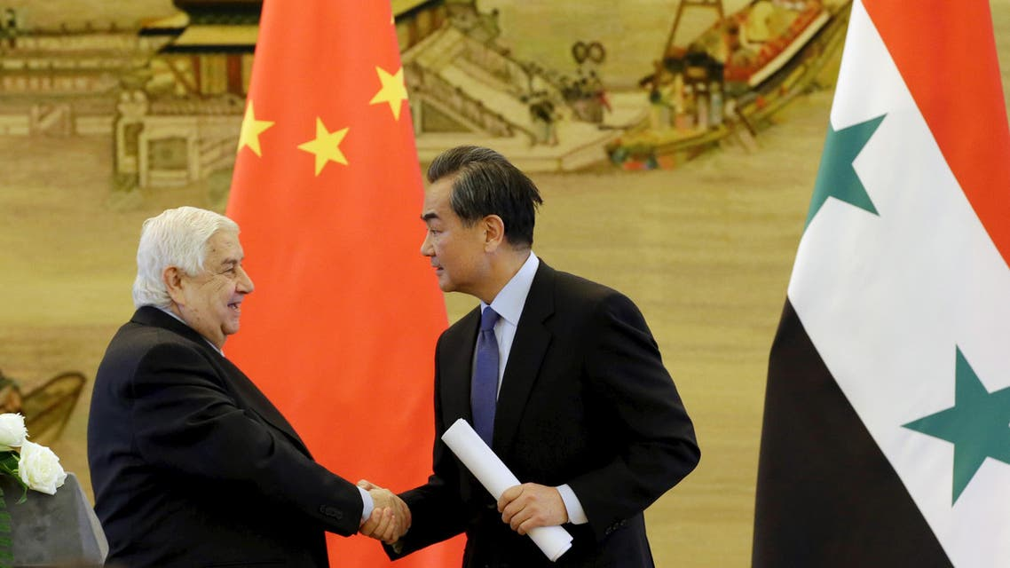 China's Foreign Minister Wang Yi (R) shakes hands with Syria's Foreign Minister Walid al-Moualem during a joint news conference after a meeting at the Ministry of Foreign Affairs in Beijing, China, December 24, 2015. REUTERS