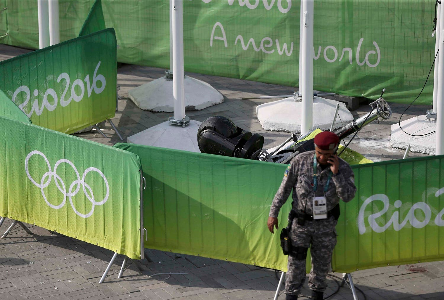 A policeman stands near an overhead television camera that fell in Rio de Janeiro. (Reuters)