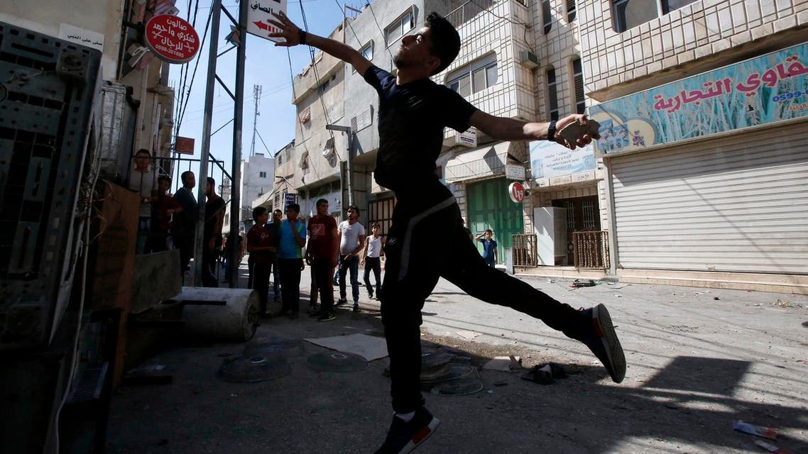 """A Palestinian youth throws stones towards Israeli soldiers as they conduct searches in the Palestinian al-Fawwar refugee camp, south of the West Bank city of Hebron, on August 16, 2016. Twenty-five Palestinians were wounded in clashes with Israeli soldiers conducting searches in a refugee camp in the southern West Bank on Tuesday, Red Crescent medics said. Some of the wounded had been hit by live ammunition, others by rubber bullets, the medics said. An Israeli army spokeswoman said the troops were conducting """"activity to uncover weaponry"""" in the camp, when """"dozens of Palestinians hurled IEDs (improvised explosive devices), blocks and rocks"""" at them. HAZEM BADER / AFP"""