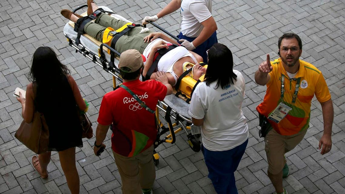 A woman is transported to an ambulance after being hit by an overhead television camera in Rio de Janeiro. (Reuters)