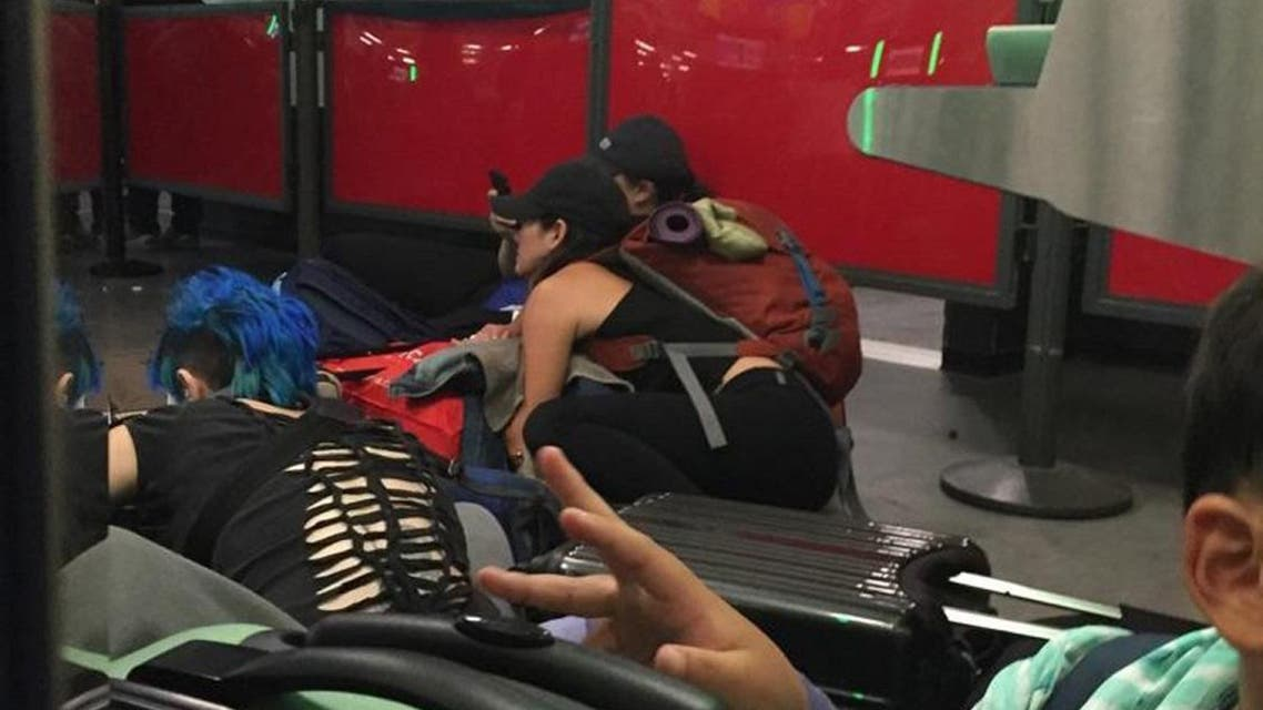 Arriving passengers in the passport control area of New York's Kennedy Airport crouch to the ground after authorities ordered them to get down on the floor in fear of a possible shooter on the loose. (AP)