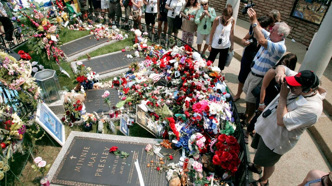 Fans visit the flower-covered grave of Elvis Presley 2007, AP