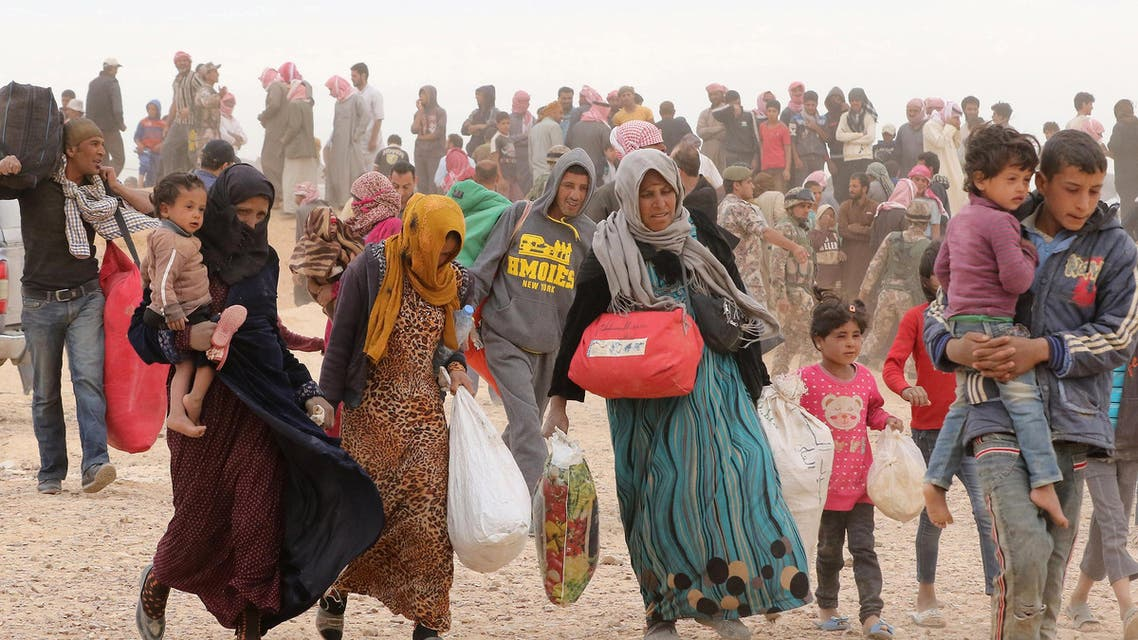 Syrian refugees carry their belongings as they wait to enter Jordanian side of the Hadalat border crossing, a military zone east of the capital Amman, after arriving from Syria on May 4, 2016. According to the Jordanian Commander of the Border Guards Brigadier Saber Al-Mahayreh, around 5000 Syrians fleeing from recent attacks on the northern Syrian city of Aleppo are trying to cross into Jordan in search of safety and most are exhausted and desperately in need of help and medical treatment. AFP