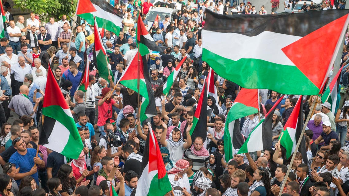"""Arab Israelis hold Palestinian flags during in a large demonstration as part of a general strike organised to support the Palestinians who call for a """"day of rage"""" on October 13, 2015 in the northern Arab-Israeli town of Sakhnin. AFP PHOTO / JACK GUEZ JACK GUEZ / AFP"""