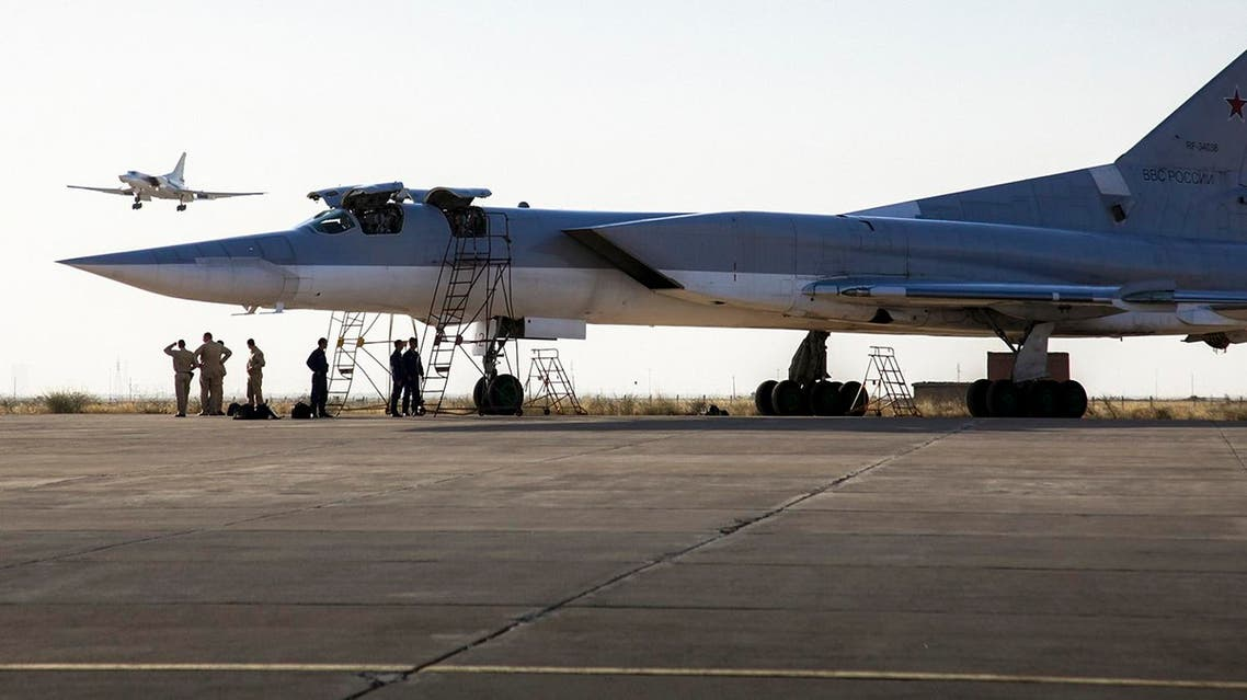 A Russian Tu-22M3 bomber stands on the tarmac while another plane lands at an air base near Hamedan, Iran. (AP)