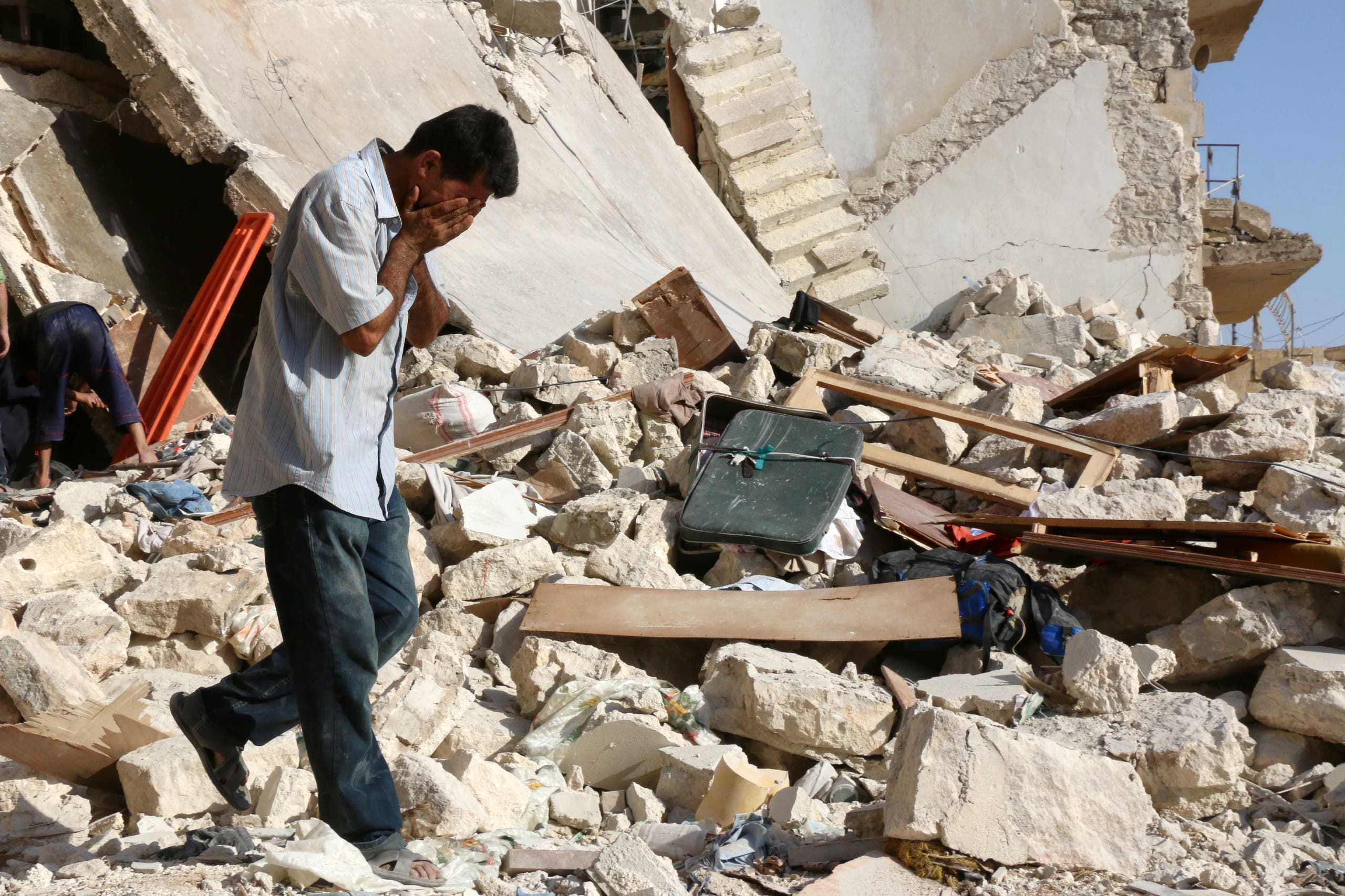 A Syrian man reacts as rescuers look for victims under the rubble of a collapsed building following a reported air strike on the rebel-held neighbourhood of Sakhur in the northern city of Aleppo on July 19, 2016
