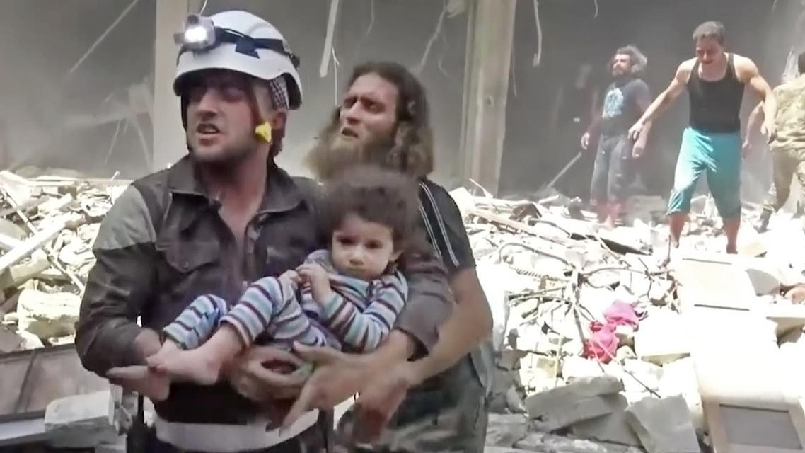 In this image made from video and posted online from Validated UGC, a Civil Defense worker carries a child after airstrikes hit Aleppo, Syria, Thursday, April 28, 2016. AP