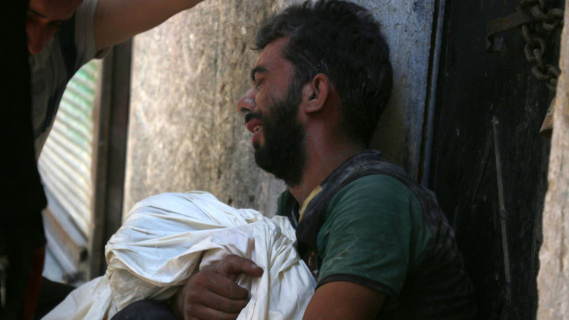 A Syrian man mourns the death of a child following reported air strikes on July 16, 2016 in the rebel-controlled neighbourhood of Saleheen in the northern Syrian city of Aleppo. AFP