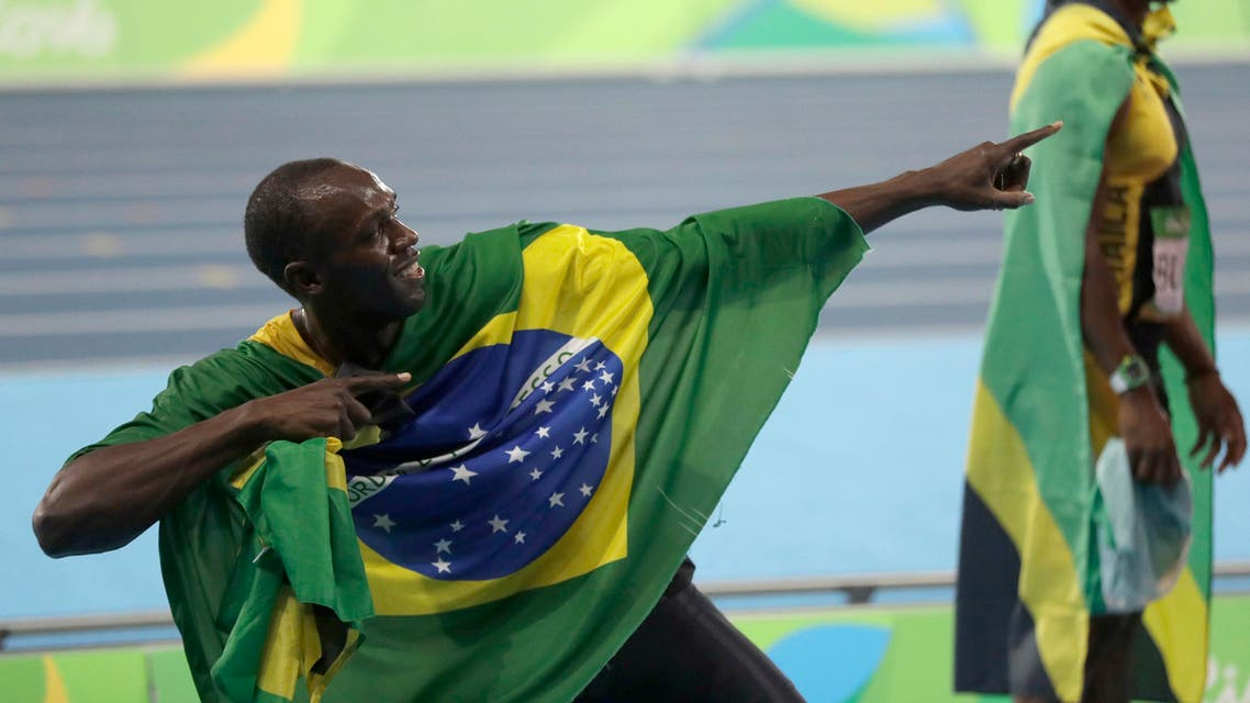 Usain Bolt holds the flag of Brazil after winning the gold medal in the men's 4x100-meter relay final during the athletics competitions of the 2016 Summer Olympics. (AP)