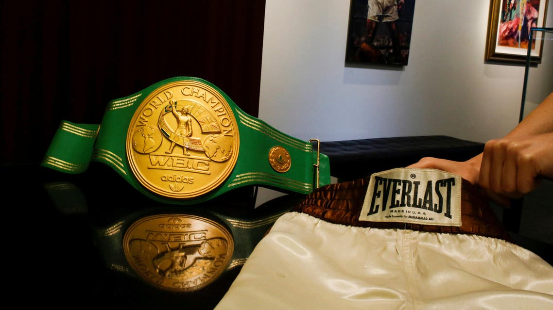 A woman arranges the short and the iconic 'Rumble in the Jungle' belt of late boxing champion Muhammad Ali at Heritage Auctions house in Manhattan, New York, US. (Reuters)