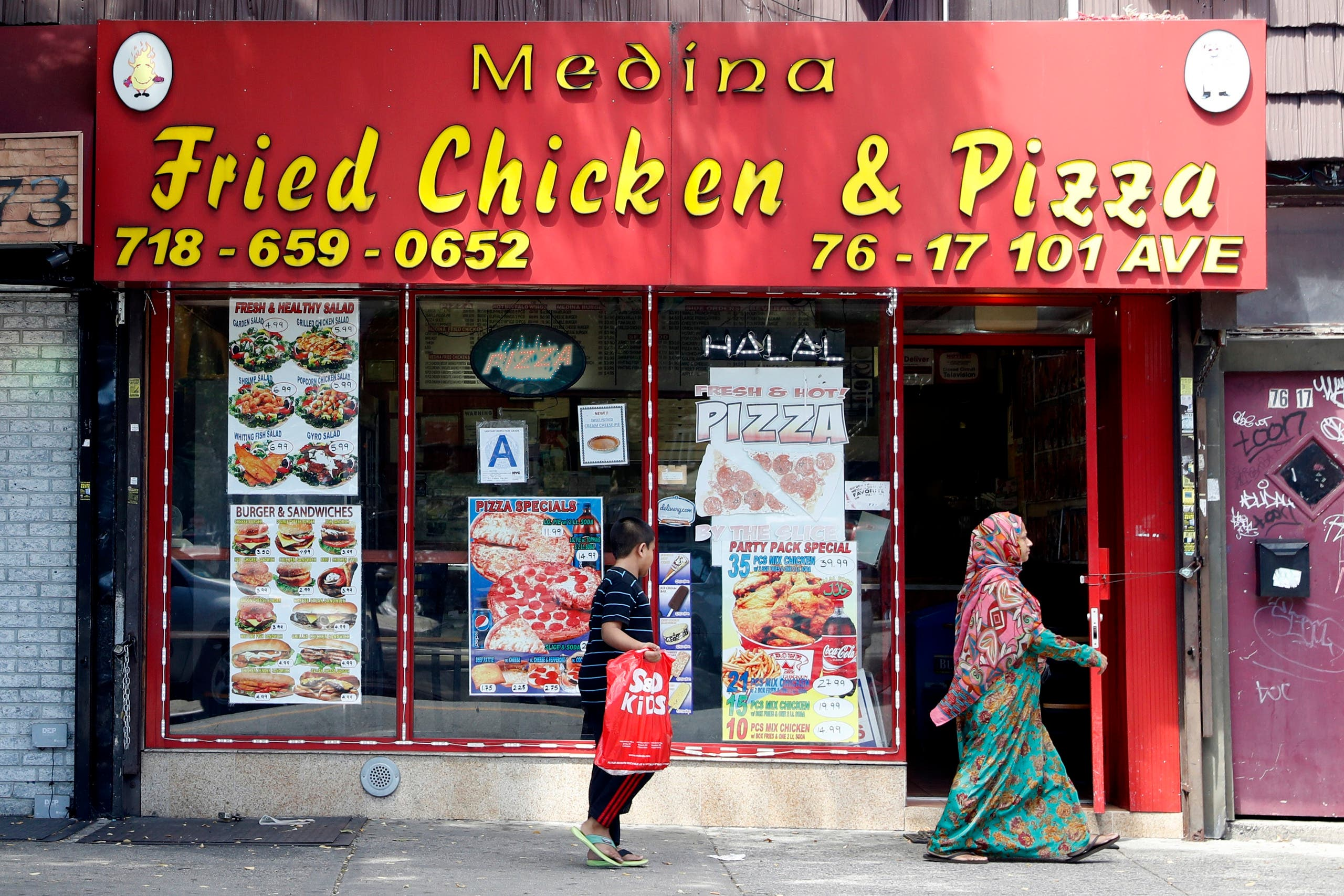 In this Wednesday, Aug. 17, 2016, photo a Muslim woman and her son walk past a Halal restaurant in the Ozone Park neighborhood of the Queens borough of New York. The shooting of an imam and his assistant near their New York mosque has unnerved Muslim residents of the Ozone Park section of Queens. (AP)