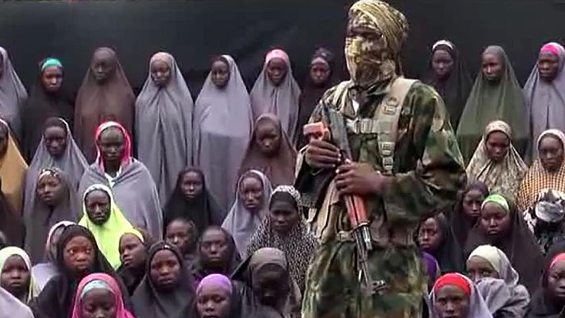 This video grab image created on August 14, 2016 taken from a video released on youtube purportedly by Islamist group Boko Haram showing what is claimed to be one of the groups fighters at an undisclosed location standing in front of girls allegedly kidnapped from Chibok in April 2014. AFP