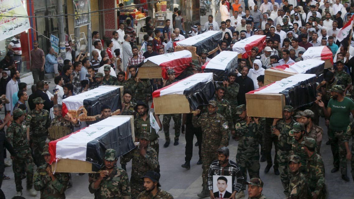 Members of Shi'ite group Asa'ib Ahl al-Haq carry the remains of Shi'ite soldiers from Camp Speicher, who were killed last summer by Islamic State militants, during the funeral ceremony in Najaf, south of Baghdad, July 1, 2015. REUTERS/