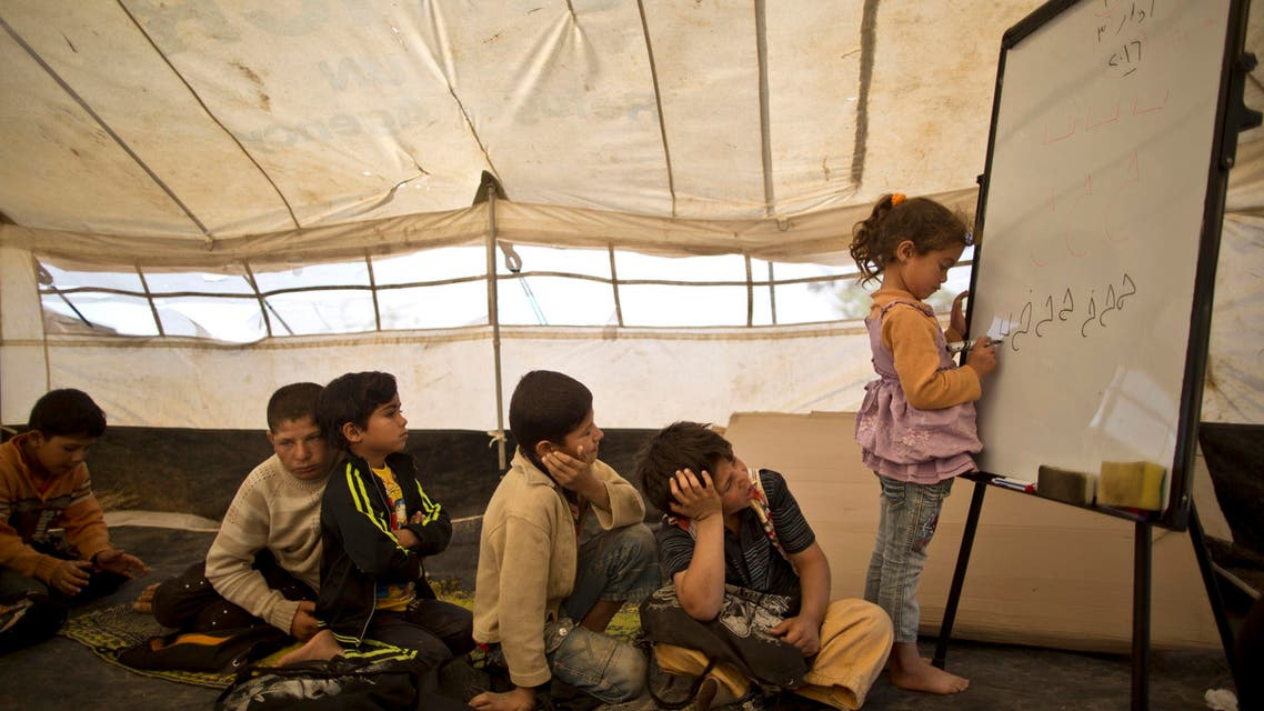 Syrian refugee Ghufran Ahmad, 5, writes on a board while she and other children attend a class at a makeshift school set up in a tent at an informal tented settlement in the Jordan Valley, Jordan, Thursday, March 31, 2016. (AP Photo/Muhammed Muheisen)