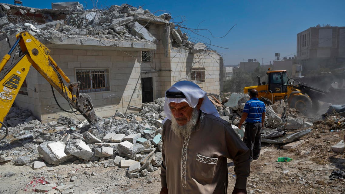 A Palestinian walks by a family house after it was demolished by Israeli troops in the West Bank village of Yatta, south of Hebron, Thursday, August 4, 2016.  (Photo: AP)