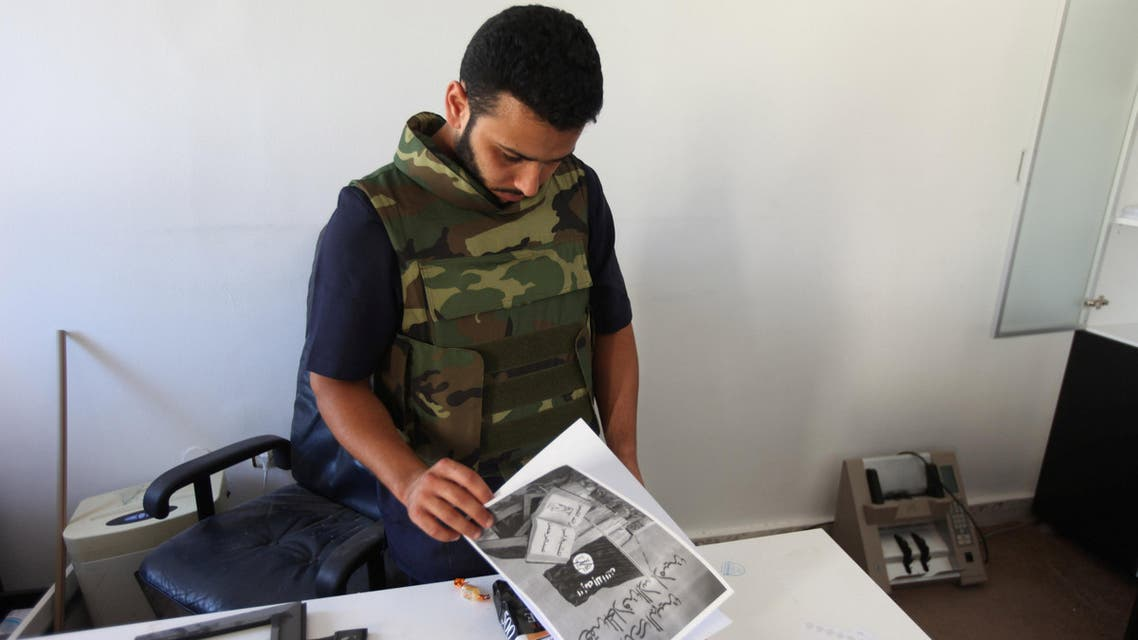 A fighter from Libyan forces allied with the U.N.-backed government checks pamphlets in an office used by Islamic State fighters after it was captured by the Libyan forces in Sirte, Libya August 22, 2016. REUTERS/Hani Amara