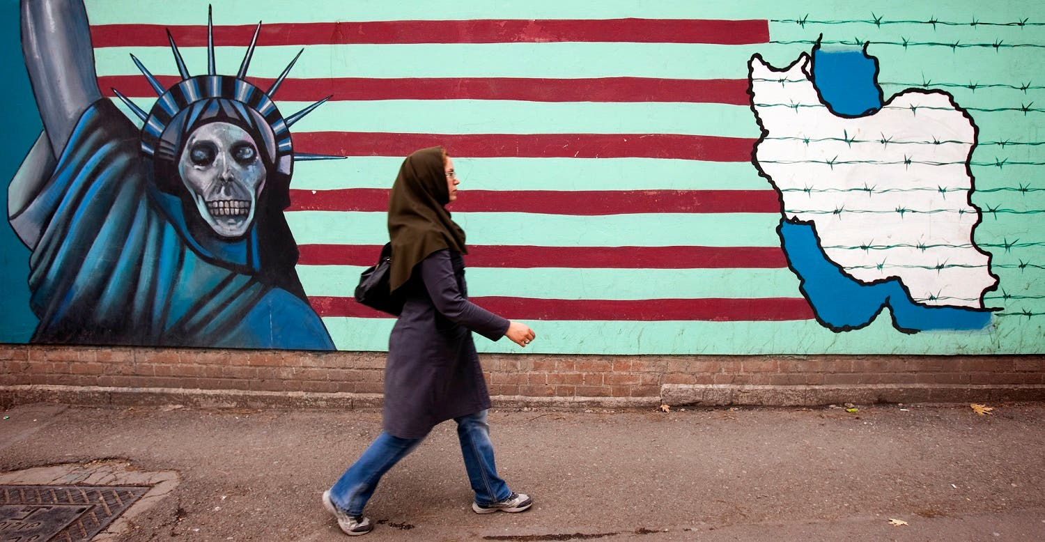 A woman walks past an anti U.S. mural at the former U.S. embassy in Tehran. (Reuters)