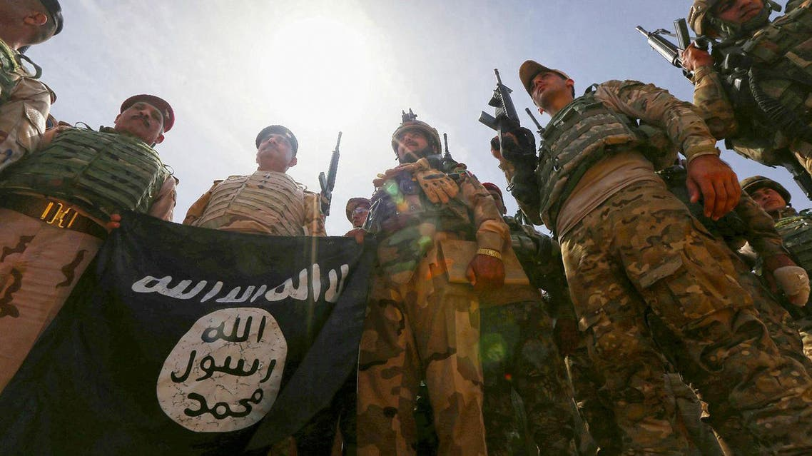 Iraqi soldiers hold a flag that they seized from ISIS as they hold a position near the frontline on April 9 in the town of Kharbardan, located 10 kms south of Qayyarah. (File photo: AFP)