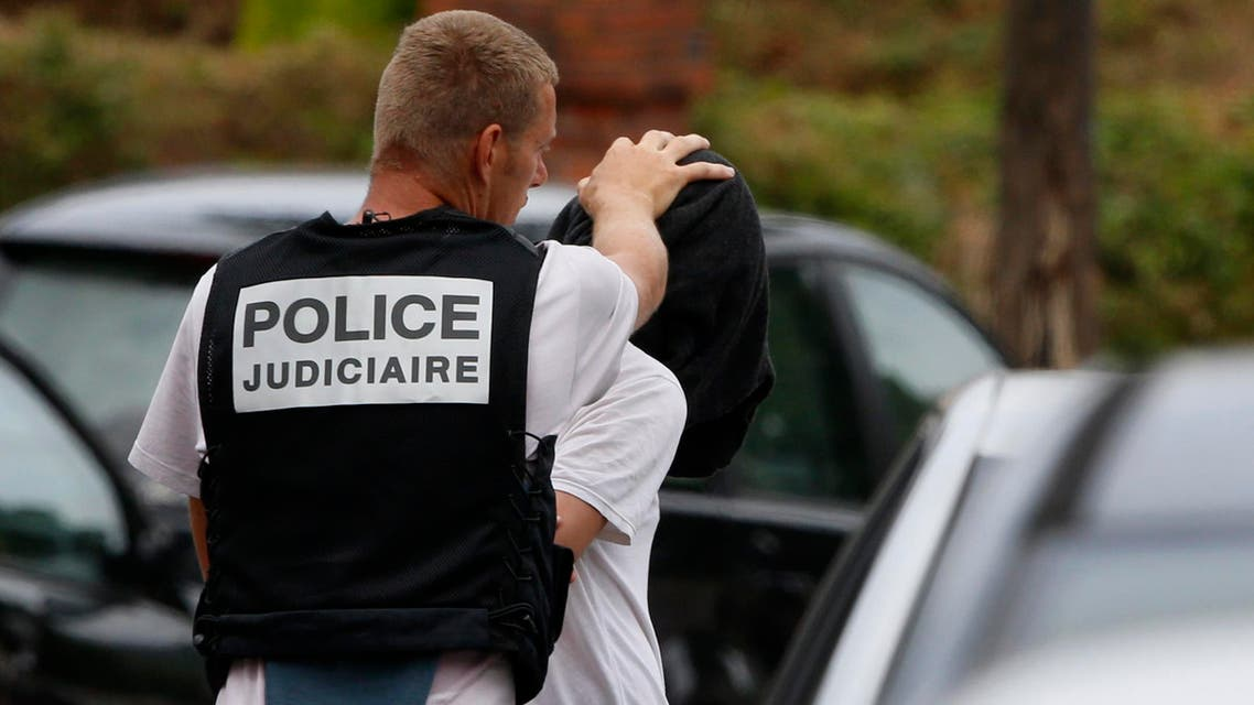French judicial investigating police apprehends a man during a raid after a hostage-taking in the church in Saint-Etienne-du-Rouvray near Rouen in Normandy, France, July 26, 2016. A priest was killed with a knife and another hostage seriously wounded in an attack on a church that was carried out by assailants linked to Islamic State. REUTERS