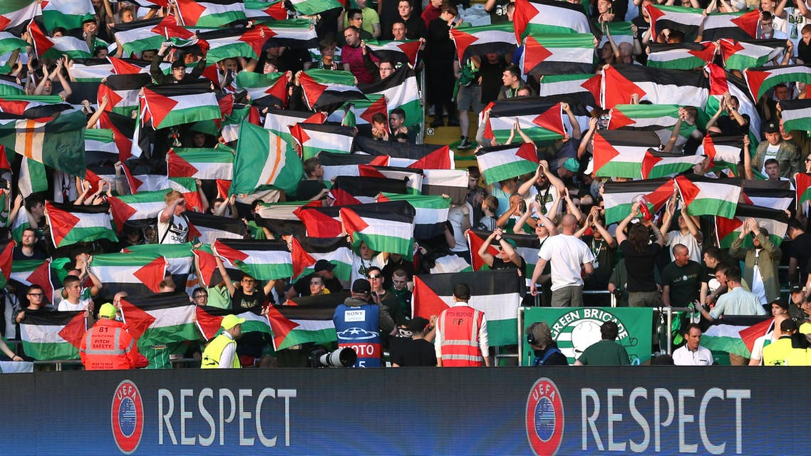 Celtic fans hold up Palestine flags reuters