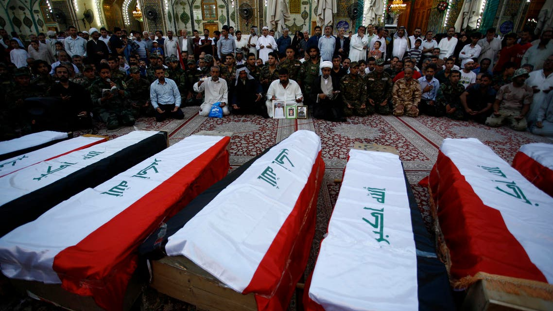 Iraqi civilians and soldiers mourn next to coffins containing the remains of ten of their comrades who were killed in the Speicher massacre, after they were handed over to relatives following weeks of examination to check their identities via DNA tests, during their funeral procession in the holy Iraqi city of Najaf on July 1, 2015. AFP