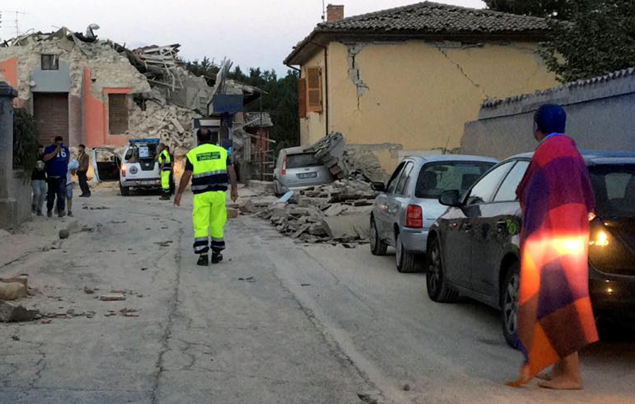 People stand along a road following a quake in Amatrice. (Reuters)