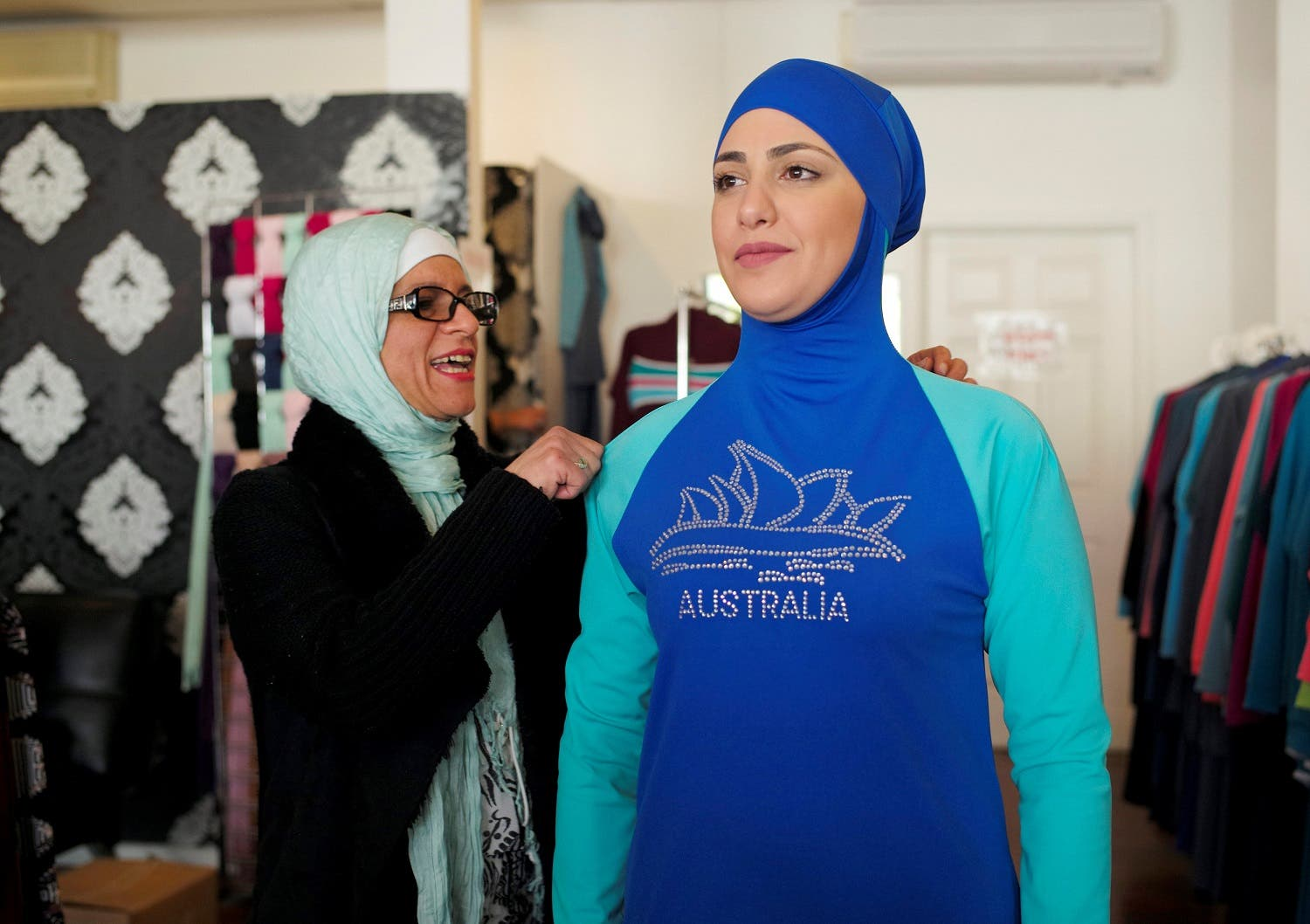 Aheda Zanetti, designer of the Burkini, adjusts one of the swim suits on model Salwa Elrashid at her fashion store in Sydney. (Reuters)
