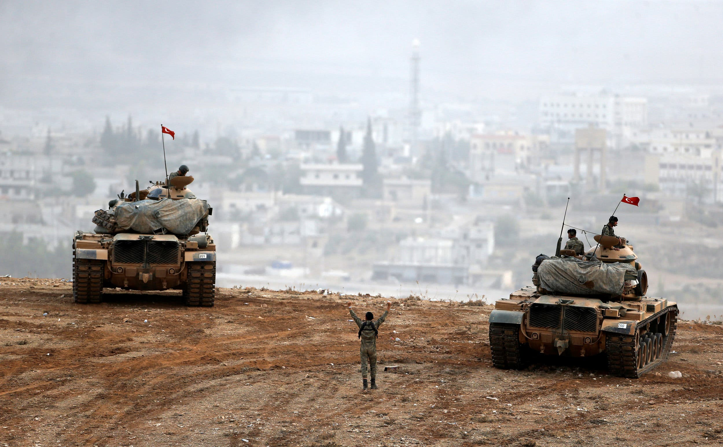Turkish army tanks take position on top of a hill near Mursitpinar border crossing in the southeastern Turkish town of Suruc in Sanliurfa province, Turkey, October 11, 2014. REUTERS