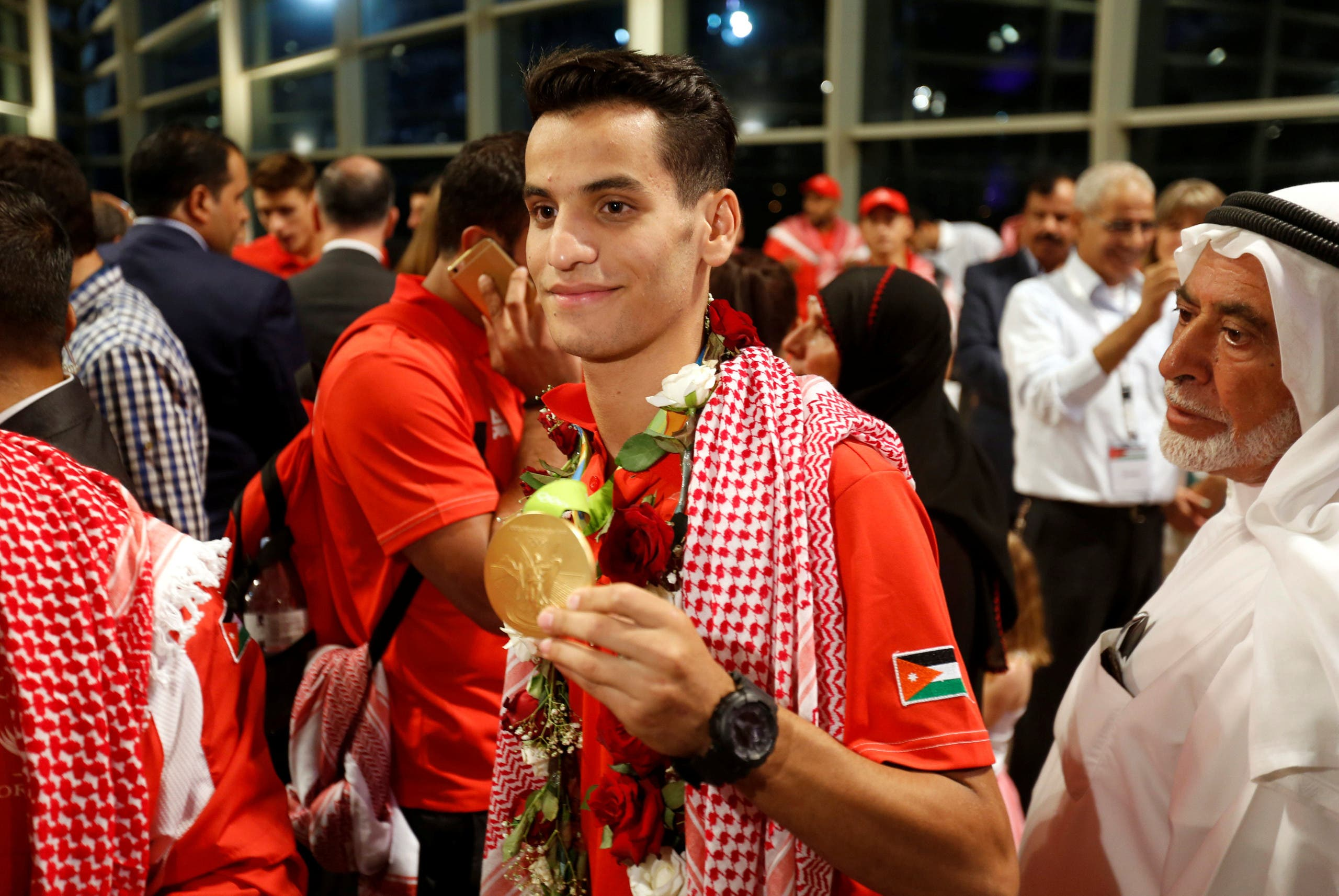 Ahmad Abughaush (C), who won a Taekwondo gold claiming Jordan's first ever Olympic medal, displays his medal for photographers upon his arrival at the Queen Alia International Airport in Amman, Jordan, August 23, 2016. REUTERS