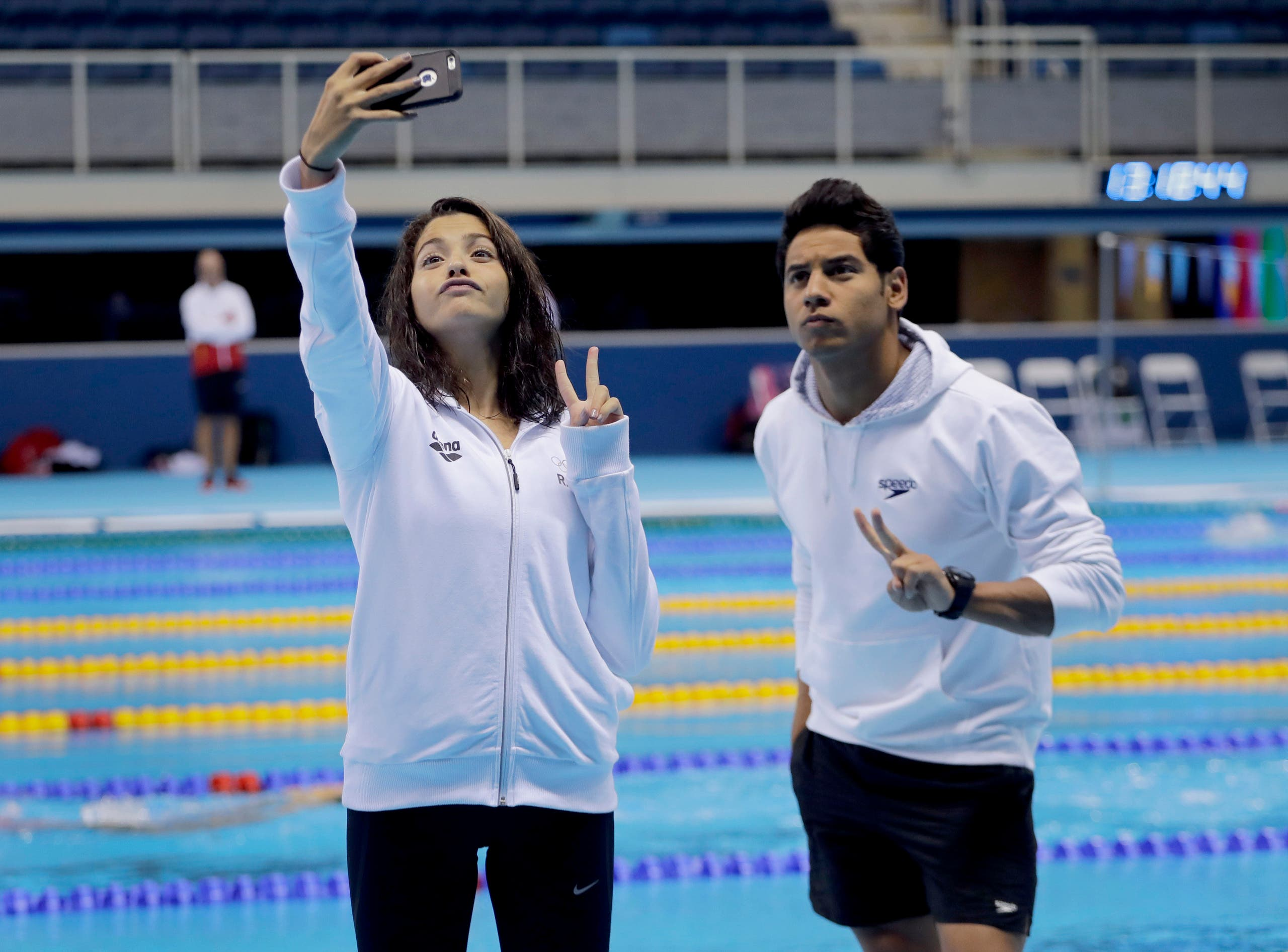 Swimmers on the Olympic refugee team Rami Anis, right, and Yusra Mardini pose for a selfie after practice at the Olympic Aquatics Stadium ahead of the Rio Olympics in Rio de Janeiro, Brazil, Thursday, July 28, 2016. AP