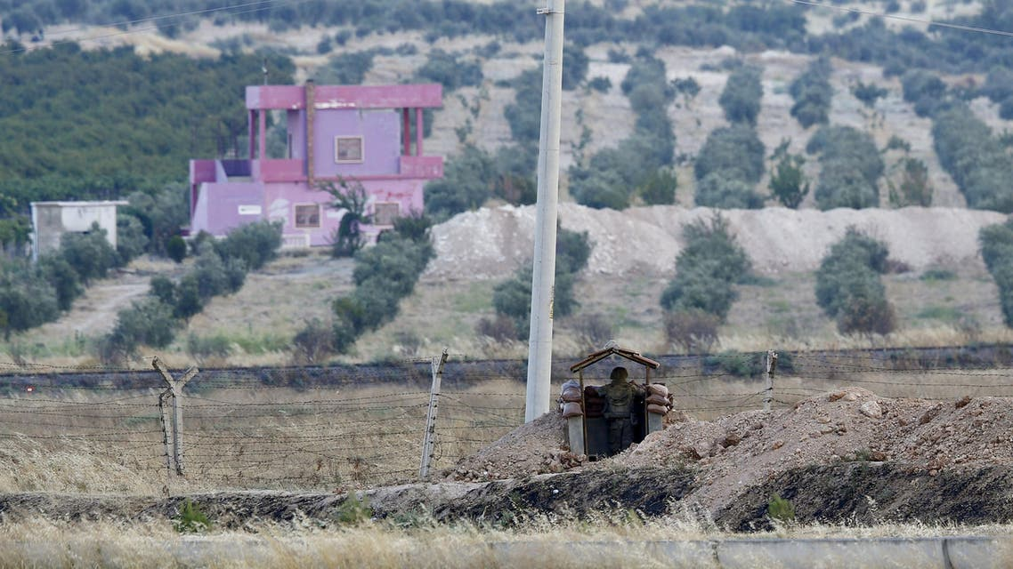 A Turkish soldier stands guard at the Turkish-Syrian border in Karkamis, bordering with the Islamic State-held Syrian town of Jarablus, in Gaziantep province, Turkey, August 1, 2015. Karkamis is a Turkish town of 10,500 people that sits directly opposite the border post. Shut for more than a year, the military sealed the crossing with a breeze block wall a few months ago. Behind it, just inside Syria, the black flag of Islamic State flaps in the breeze. Karkamis lies on the northeastern edge of a rectangle of Syrian territory some 80 km (50 miles) long, controlled by the radical Islamists. The United States and Turkey hope that by sweeping Islamic State from this border zone, they can deprive it of a smuggling route which has seen its ranks swollen with foreign fighters and its coffers boosted by illicit trade. Picture taken August 1, 2015. REUTERS