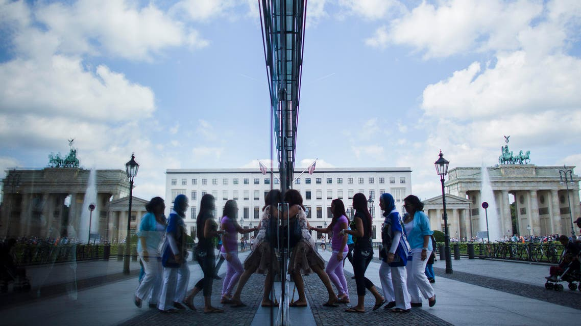People are reflected in a window as they enter a building in front of Germany's landmark Brandenburg Gate in Berlin, Germany