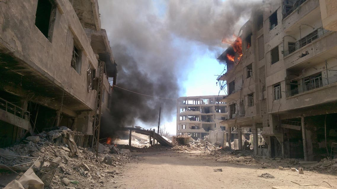 Fire and smoke gush out of buildings following reported air strikes on the Syrian besieged rebel-held town of Daraya near the capital Damascus on August 16, 2016.  afp