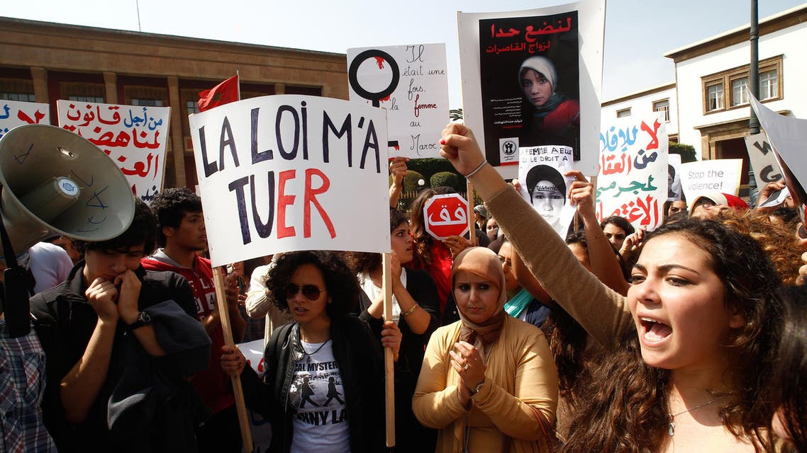 In this March 17, 2012 file photo, women hold posters as they protest in support of Amina Filali who committed suicide in March 2012 in front the Moroccan parliament in Rabat, Morocco. (AP)