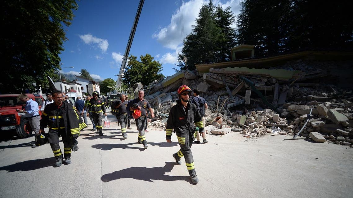 Firefighters walk past a damaged house in the central Italian village of Amatrice. (AFP)