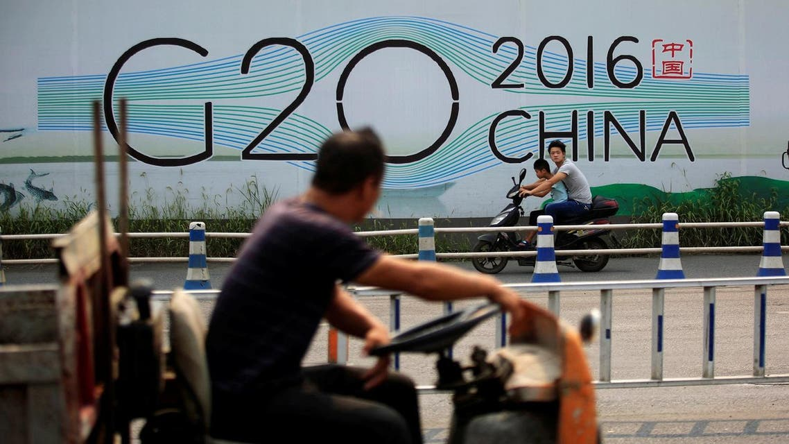 People cycle past a billboard for the upcoming G20 summit in Hangzhou. (Reuters)