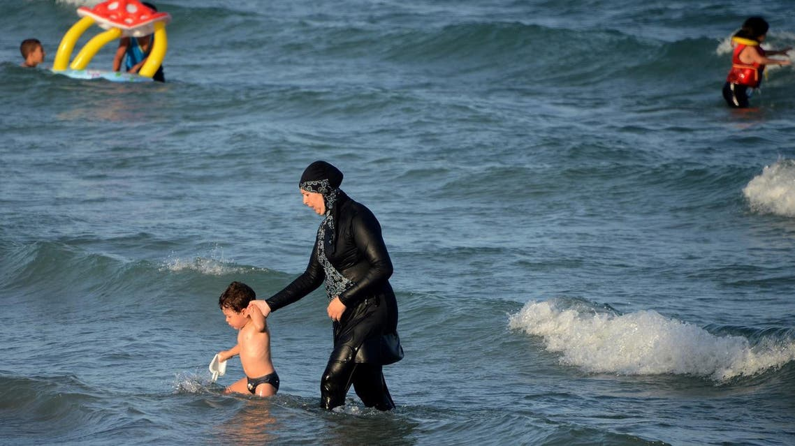 "A Tunisian woman wearing a ""burkini"", a full-body swimsuit designed for Muslim women, walks in the water with a child on Aug. 16, 2016 (File Photo: AFP)"