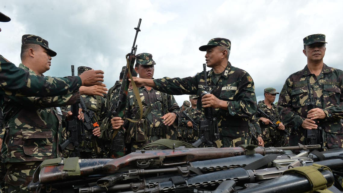 Philippine military officers hand over newly acquired M4 assault rifles to their troops during a distribution ceremony at Fort Magsaysay army training camp in Nueva Ecija, north of Manila on September 4, 2014. Around 50,000 M4 assault rifles will be distributed to military personnel at the end of the year, as the military chief vowed, the poorly-armed military said it would stand up to China in the increasingly-tense dispute over territory in the South China Sea. AFP PHOTO/TED ALJIBE