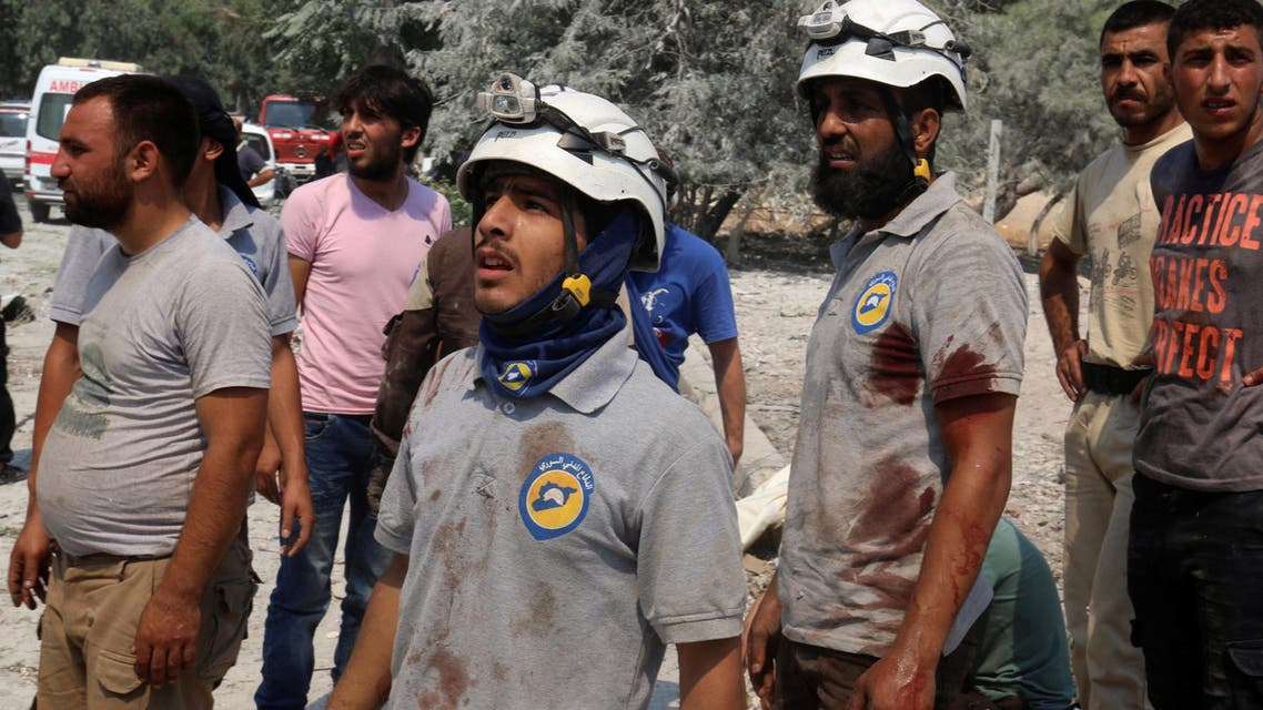 Civil Defence members with blood on their shirts stand after double airstrikes on the rebel held Bab al-Nairab neighborhood of Aleppo. (Photo: Reuters)