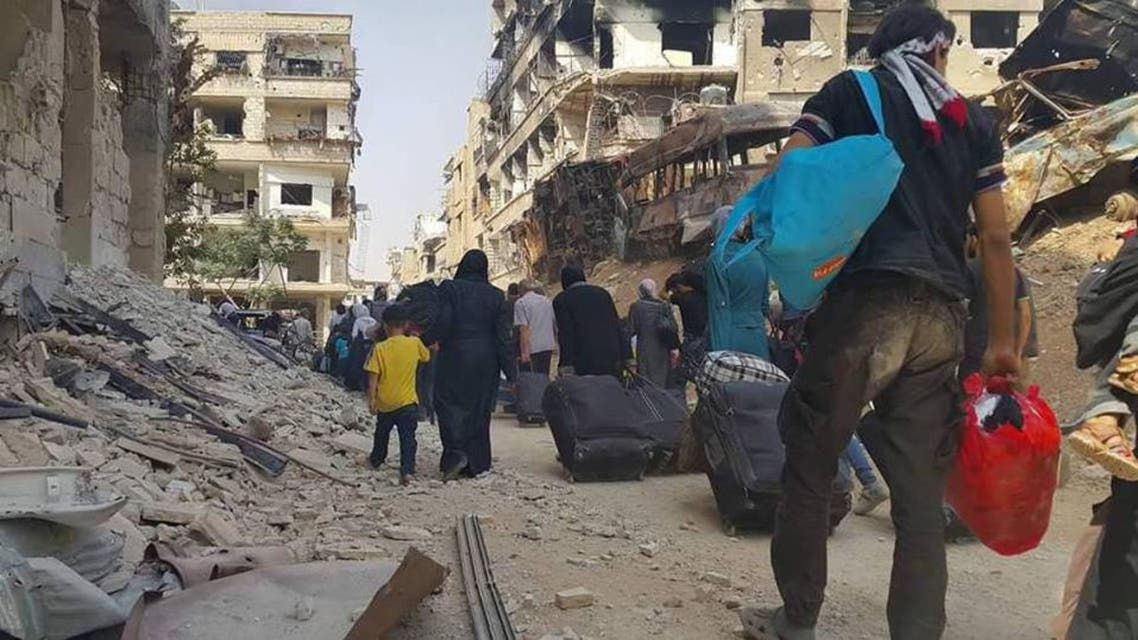 People carry their belongings before being evacuated from the besieged Damascus suburb of Daraya, after an agreement reached on Thursday between rebels and Syria's army, in this handout picture provided by SANA on August 26, 2016. Reuters