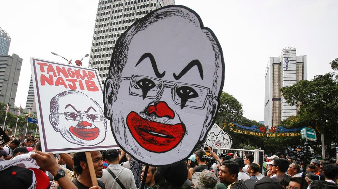 """Student activists holds up a caricature of Malaysian Prime Minister Najib Razak during a rally calling for the arrest of """"Malaysian Official 1"""" in Kuala Lumpur, Malaysia, Saturday, Aug. 27, 2016. Malaysian student activists have rallied to demand the arrest of Prime Minister Najib Razak, who has been implicated in a U.S. government probe into a massive fraud in a Malaysian investment fund. (AP Photo/Joshua Paul)"""