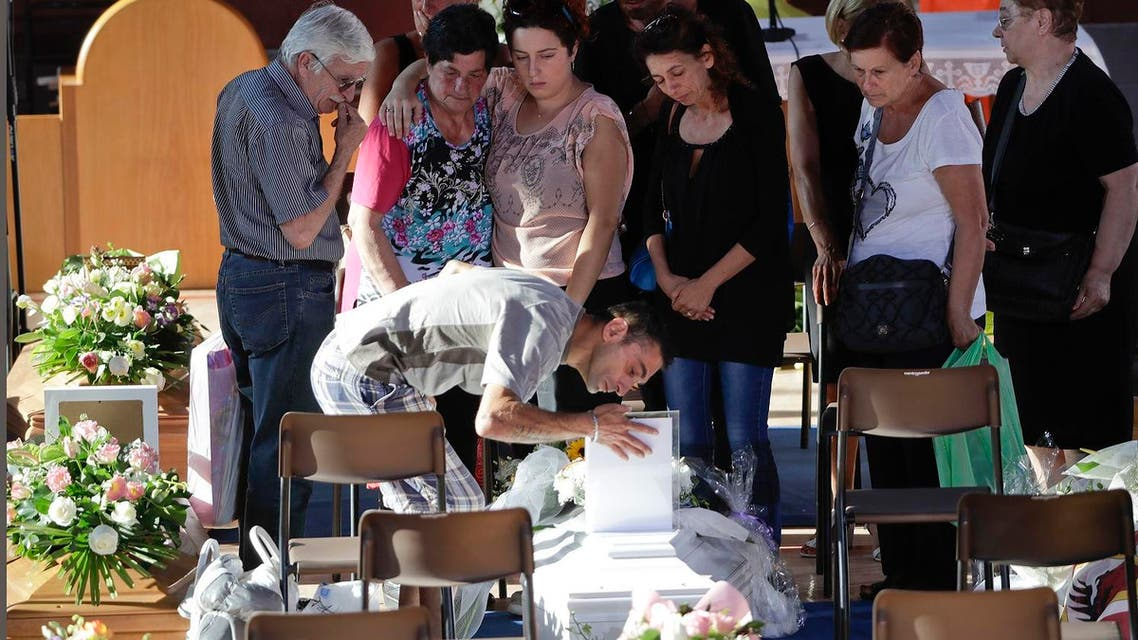 Relatives mourn over a coffin of one of the earthquake victims prior to the start of the funeral service in Ascoli Piceno, Italy, Saturday, Aug. 27, 2016. Rescue crews, rattled by aftershocks, dug through crumbled homes looking for quake survivors as donations began pouring into the area and Italy again anguished over its failure to protect ancient towns and modern cities from the country's highly seismic terrain. (AP Photo/Gregorio Borgia)