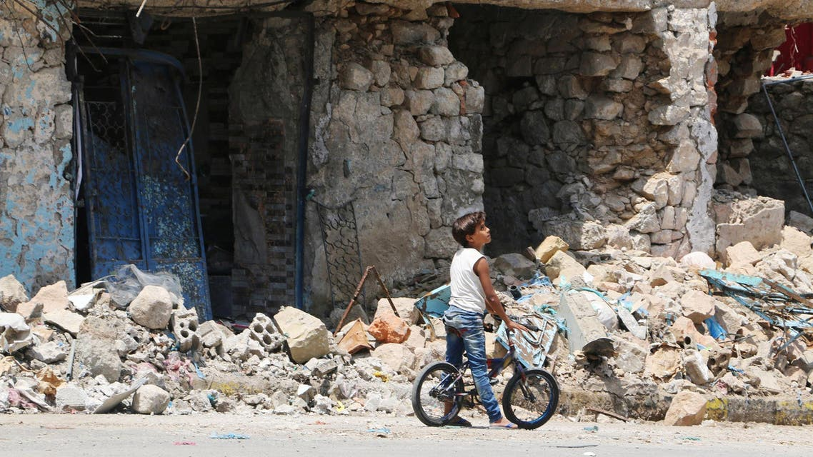 A boy with his bicycle stands near buildings destroyed during fighting between tribal fighters and Shiite rebels known as Houthis at a street in Taiz, Yemen, Sunday, Aug. 23, 2015. (AP)