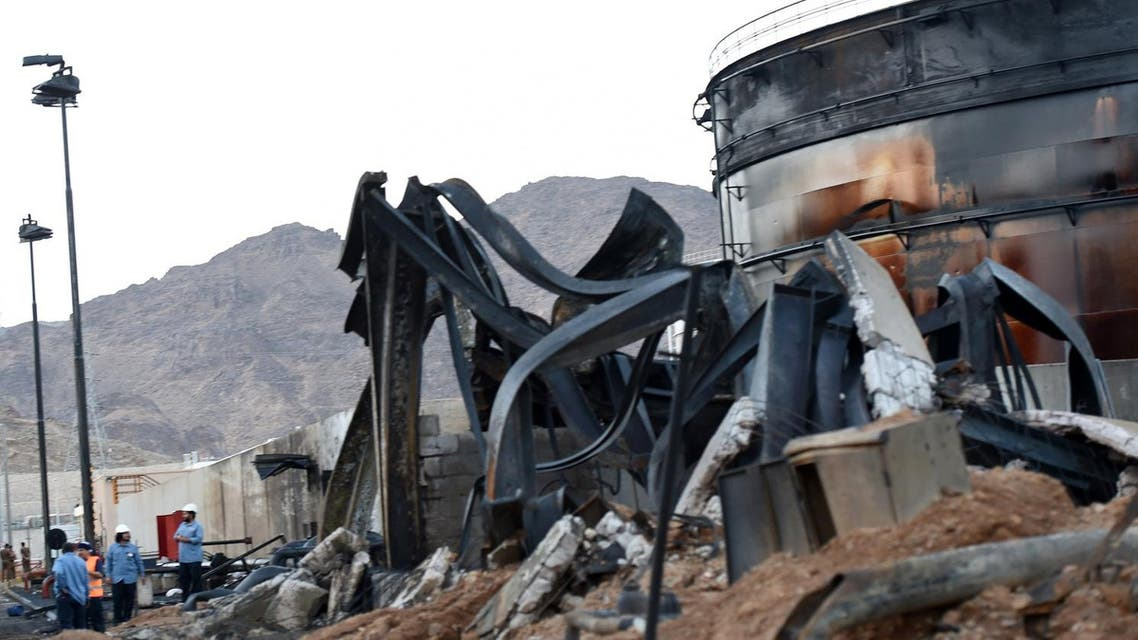 Saudi and foreign workers talk next to a burnt tank at a power station on August 27, 2016 in the Saudi border city of Najran, a day after it was struck by a rocket fired from Yemen. The attack on the transformer in Najran, which lies just across the Yemen border, marks a rare hit on Saudi Arabia's infrastructure after months of periodic bombardment of the area. Cross-border attacks into Saudi Arabia have intensified since the suspension in early August of UN-brokered peace talks between the Shiite Huthi rebels and their allies, and Yemen's internationally-recognised government which has the military support of a Saudi-led Arab coalition. FAYEZ NURELDINE / AFP