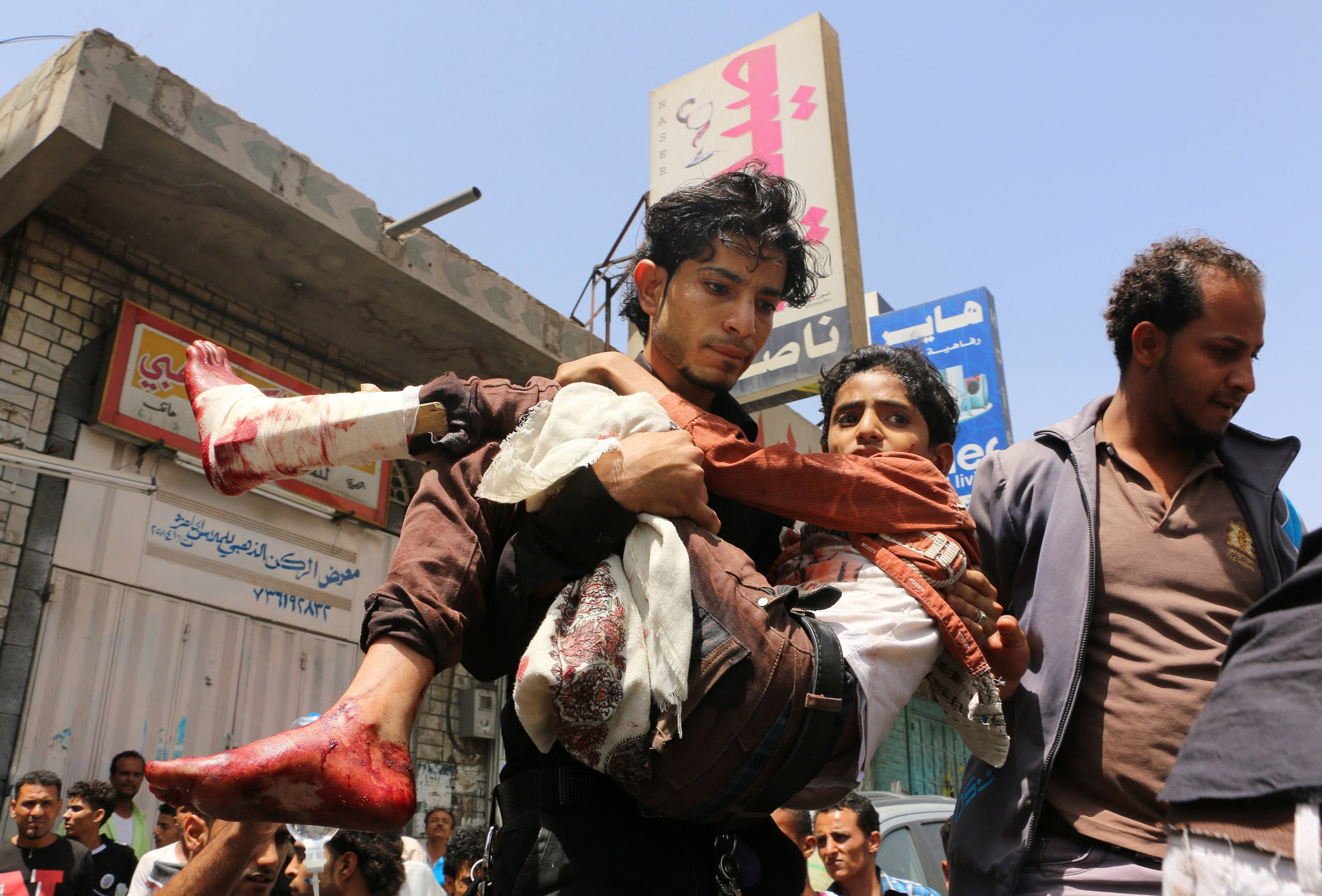 In this April 26, 2015, file photo, a man carries a boy who was injured during a crossfire between tribal fighters and Shiite militia known as Houthis, in Taiz, Yemen. (Reuters)