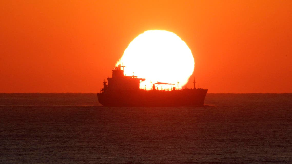 A cargo vessel passes by as the sun rises over the Indian Ocean in Durban, South Africa, on Saturday June 19, 2010. (AP)