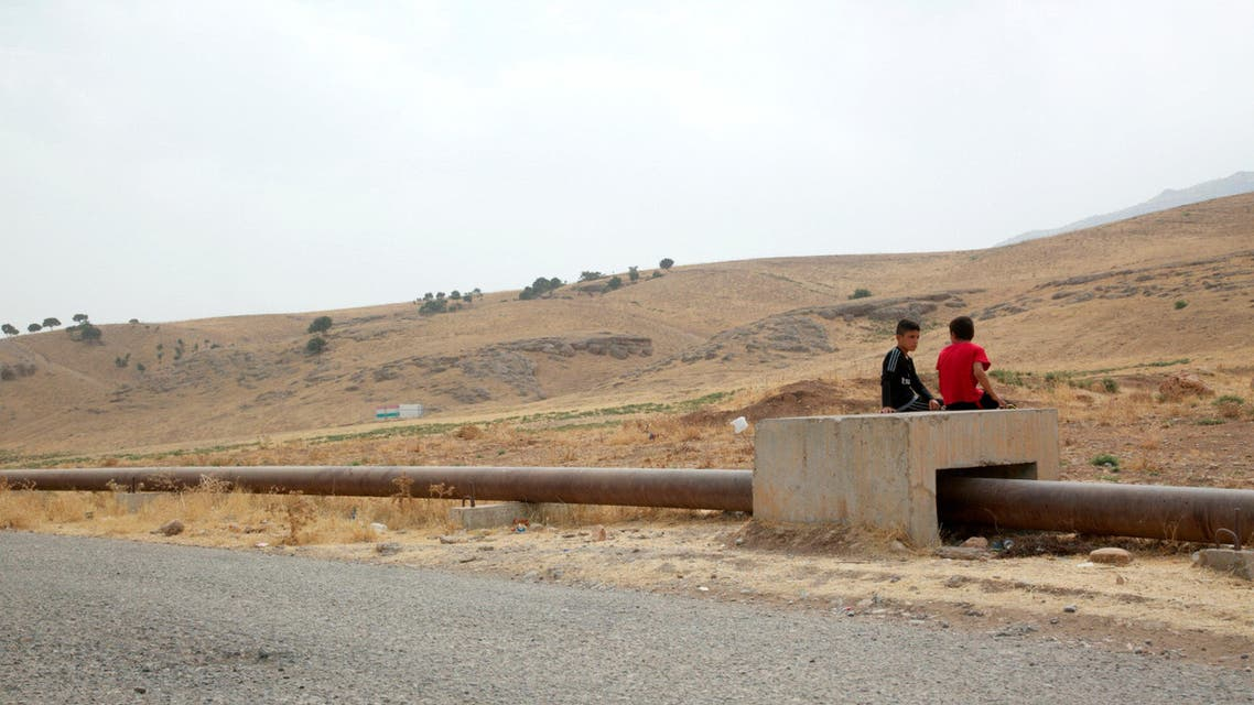 Boys sit on the Iraqi-Turkish pipeline in Zakho district of the Dohuk Governorate of the Iraqi Kurdistan province, Iraq, August 28, 2016. Reuters