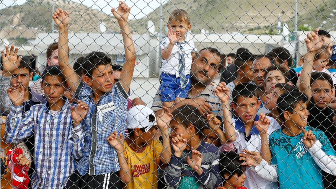 Refugees and their children wait for the arrival of German Chancellor Angela Merkel, Turkish Prime Minister Ahmet Davutoglu, EU Council President Donald Tusk and European Commission Vice-President Frans Timmermans (all not pictured) at Nizip refugee camp near Gaziantep, Turkey, April 23, 2016. REUTERS