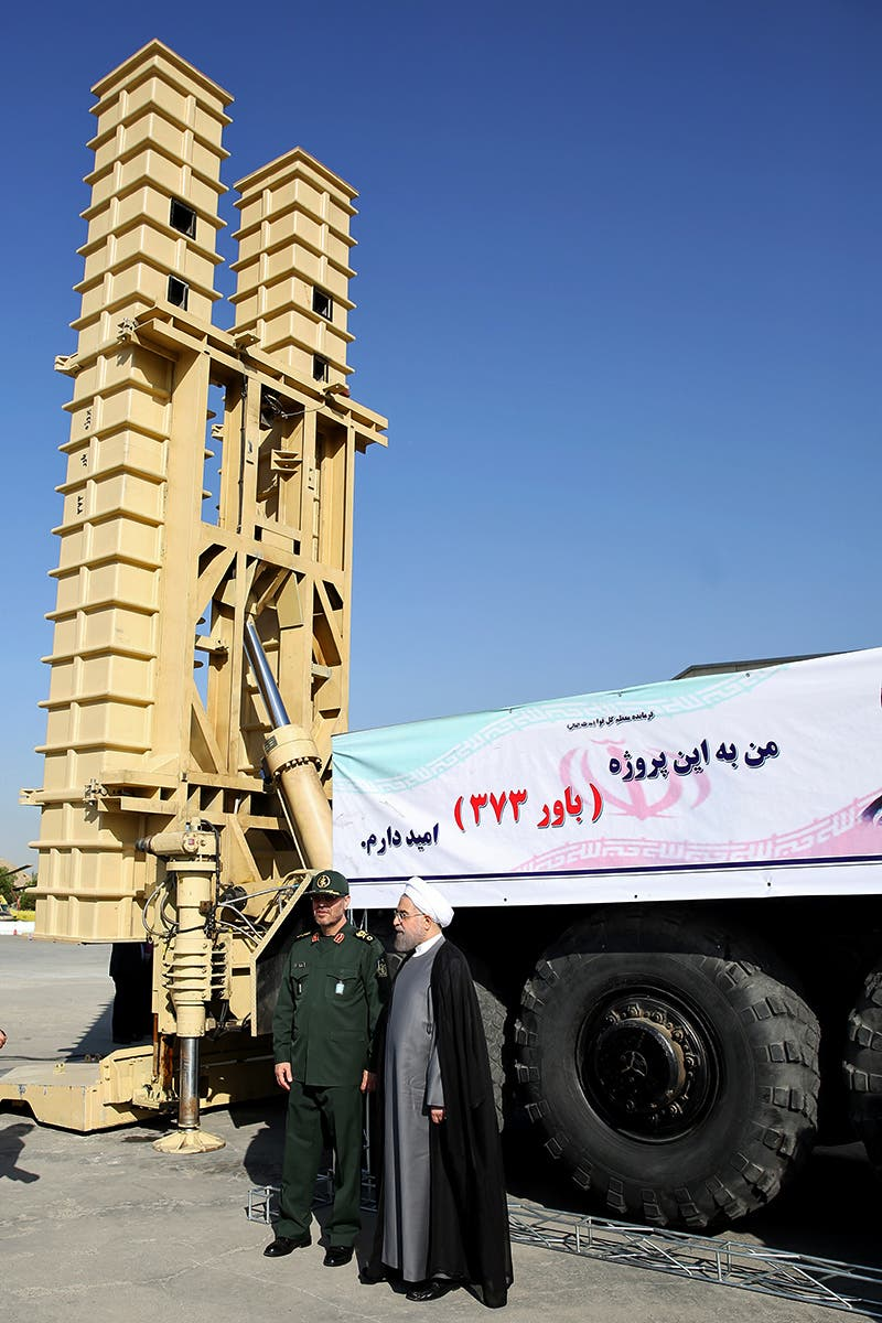 Iranian President Hassan Rouhani (C) and Iranian Defense Minister Hossein Dehghan (L) stand next to the new Bavar 373 missile defense system in Tehran. afp